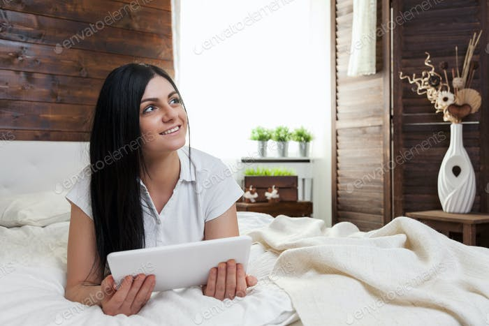 Beautiful woman relaxing on the bed and using her tablet
