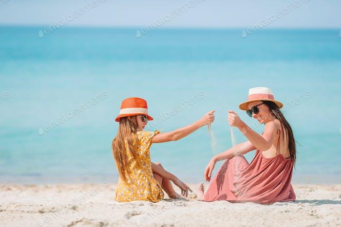 Schöne Mutter und Tochter am karibischen Strand genießen Sommerurlaub