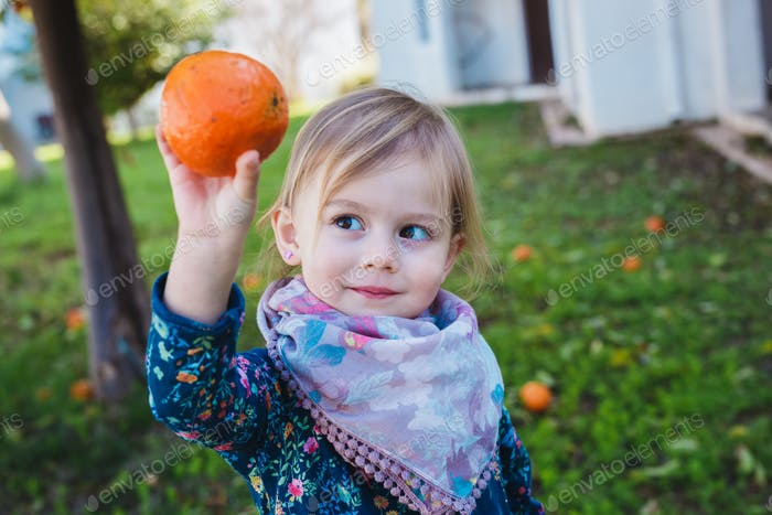 Cute baby girl showing orange