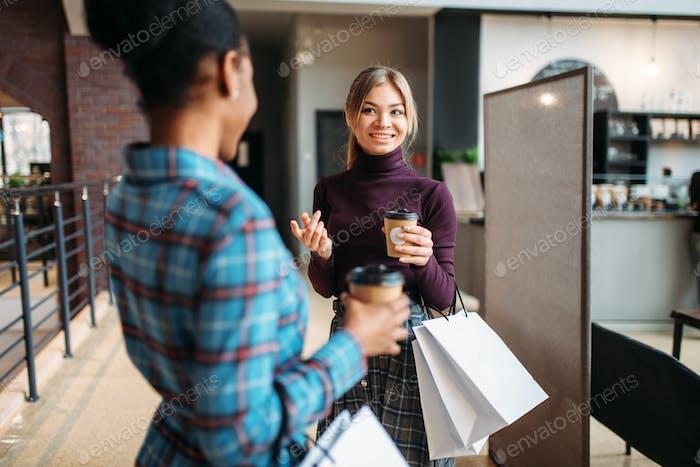 Weiße und schwarze Frauen mit Einkaufstaschen im Einkaufszentrum