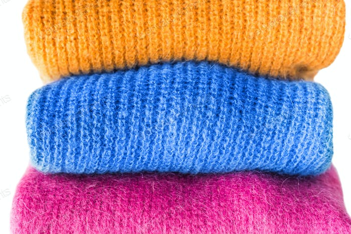 Pile of color woolen sweaters with classic blue one
