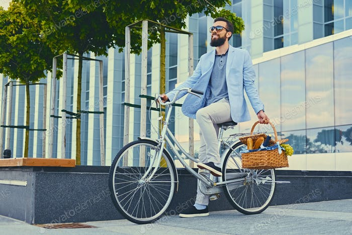 Ein Mann auf einem Stadtrad hält Picknickkorb.