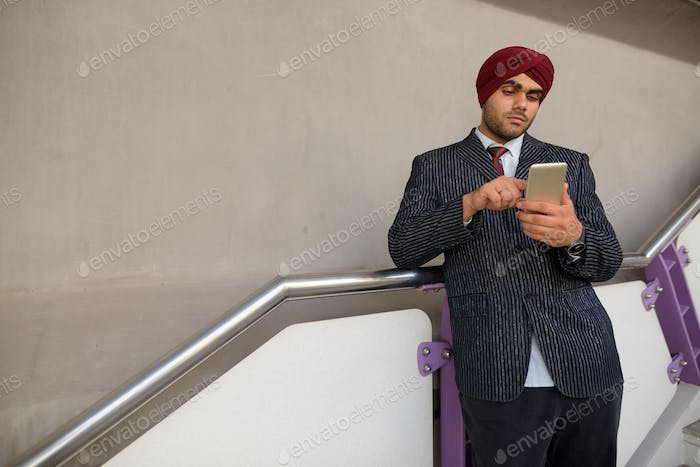 Indian businessman with turban outdoors at train station