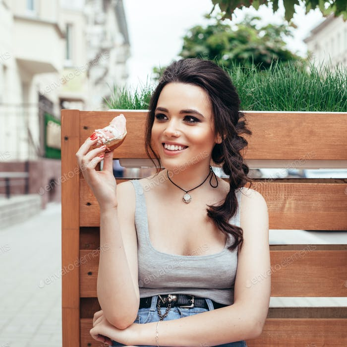 Happy smiling girl eating a donut
