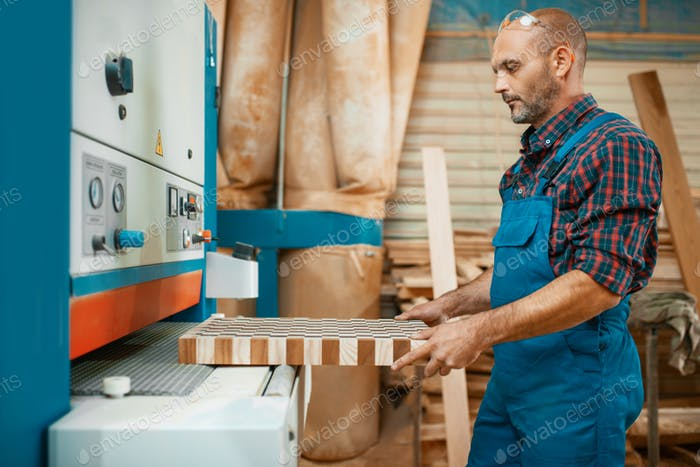 Carpenter works on woodworking machine, factory