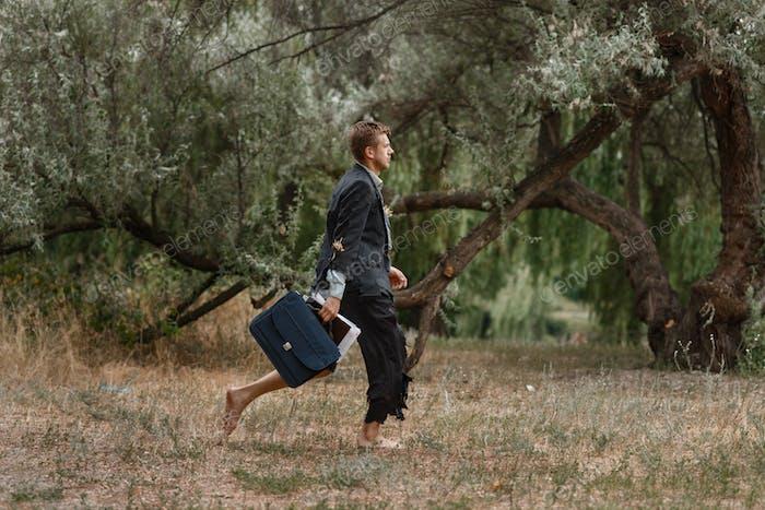 Businessman in torn suit walking on desert island