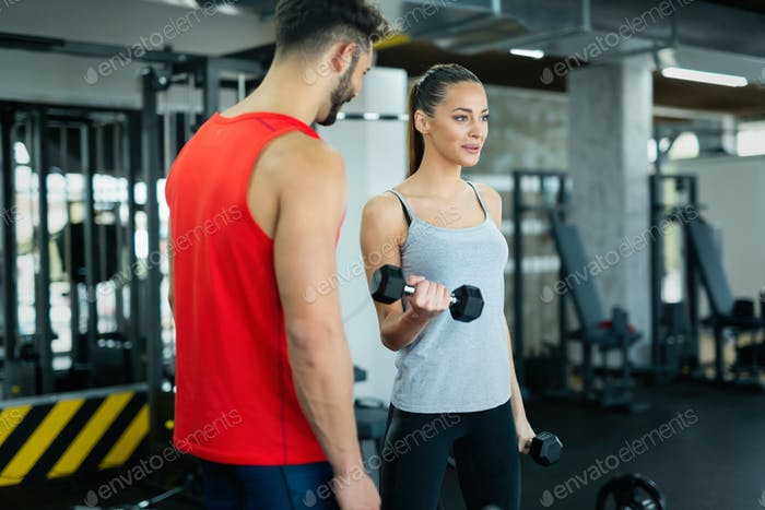 Young adult woman working out in gym with trainer