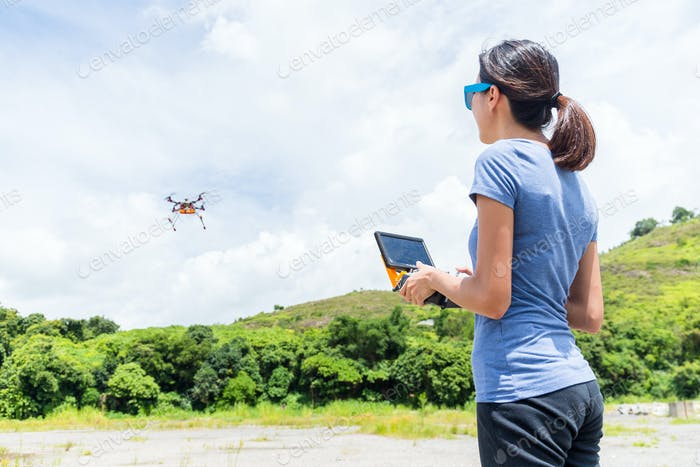 Young Woman remote flying drone