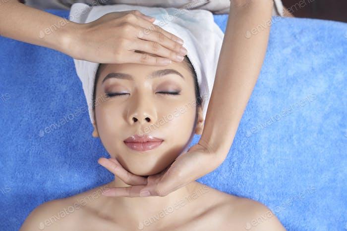Sensual woman enjoying face massage