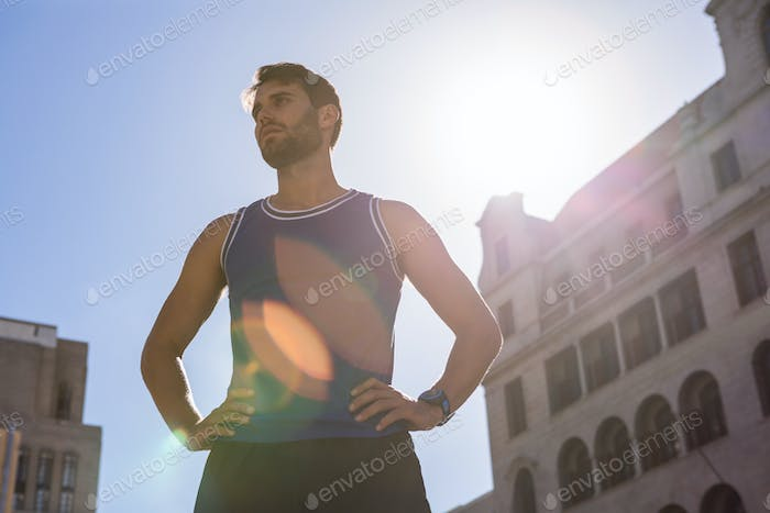 Handsome athlete with hands on hips in the city