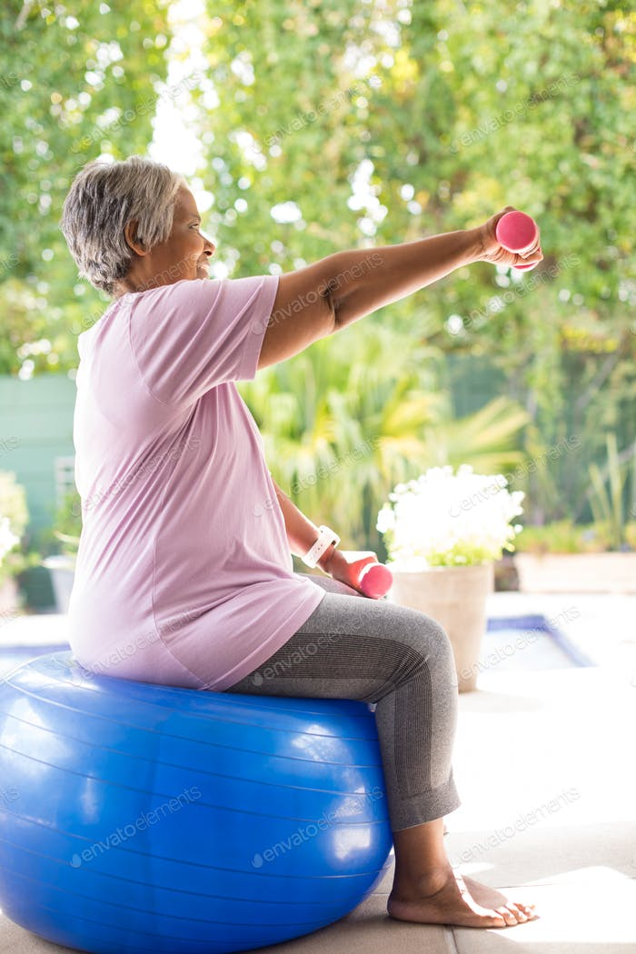 Side view of senior woman lifting dumbbells while exercising