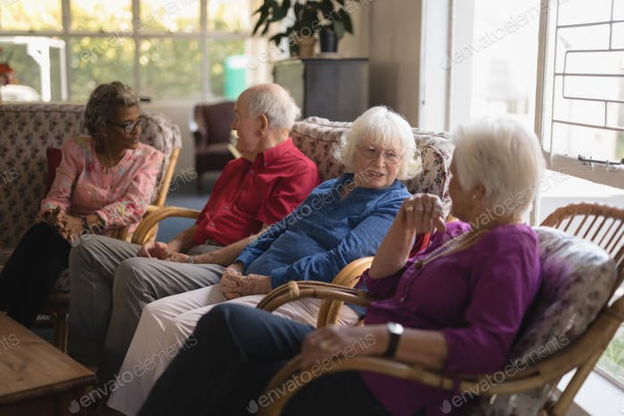 Side view of group of senior friends interacting with each other at nursing home