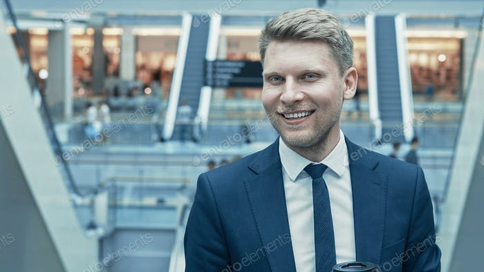 Smiling businessman in suit in the store