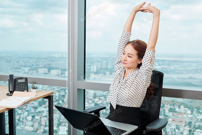 Businesswoman stretching in her chair