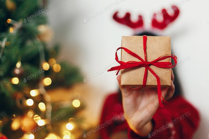 Woman with reindeer hat holding present in front