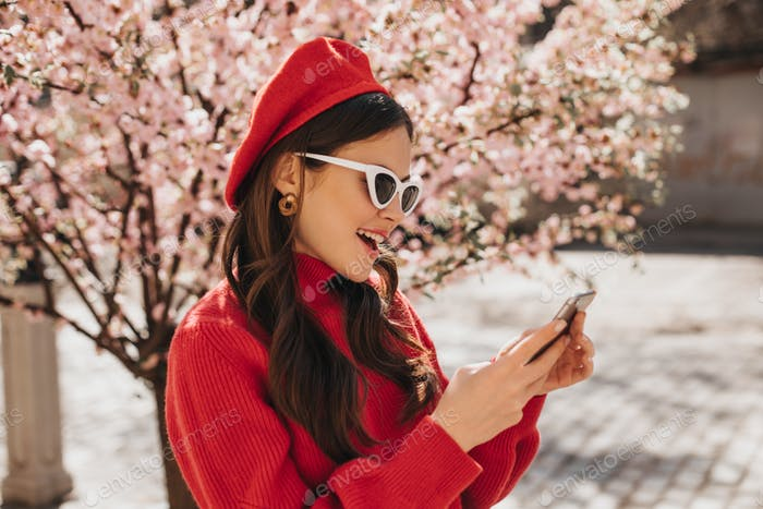 Beautiful woman in beret and sunglasses is chatting on phone near Sakura. Outside portrait of lady