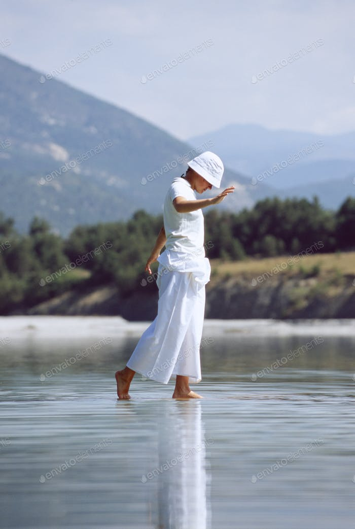 Young woman walking in lake