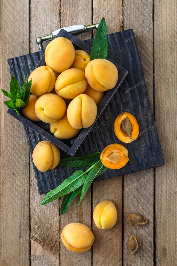 Delicious ripe apricots in a wooden box on the table, top view