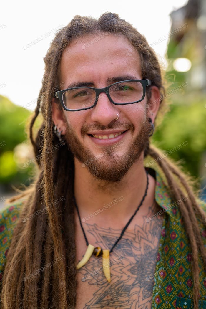 Young handsome Hispanic tourist man with dreadlocks in the stree