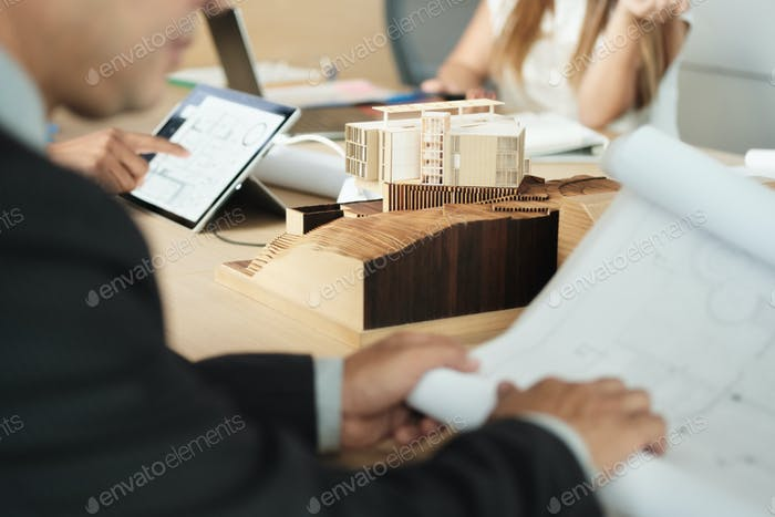 Miniature Building At Business Meeting With Architect Looking at Blueprints