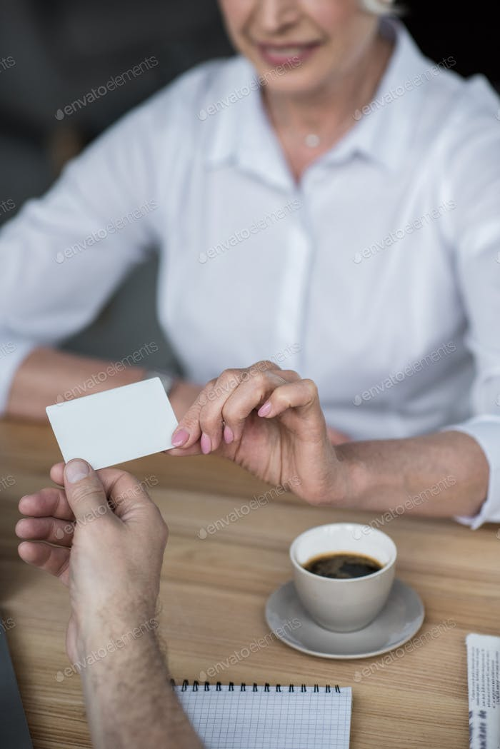 Businessman giving business card to female client