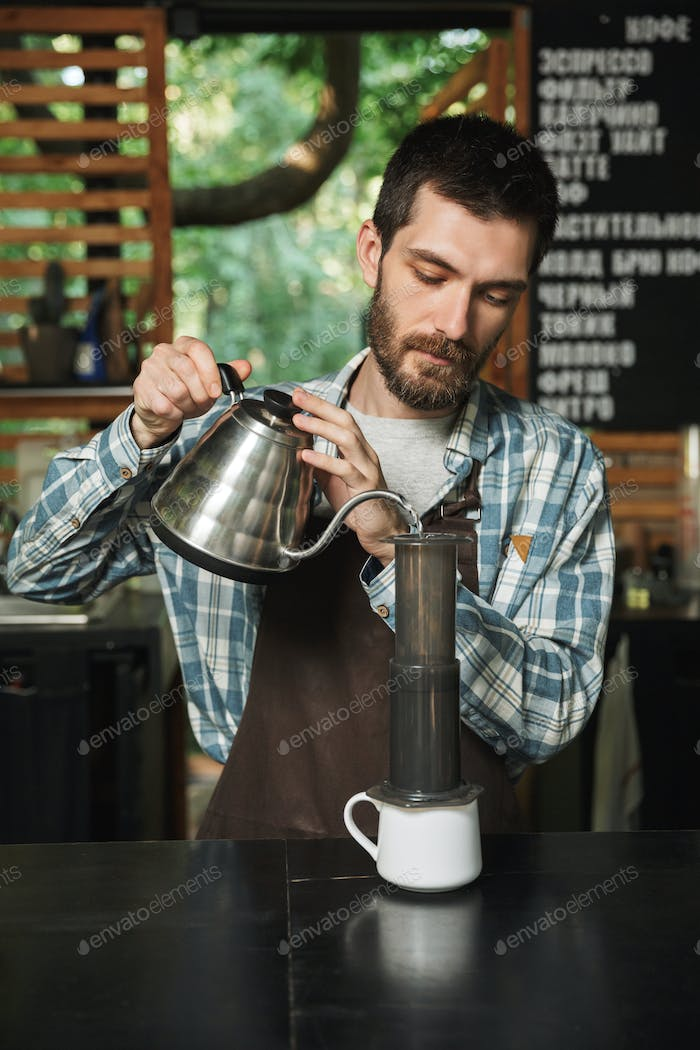 Portrait of european barista man making coffee while working in