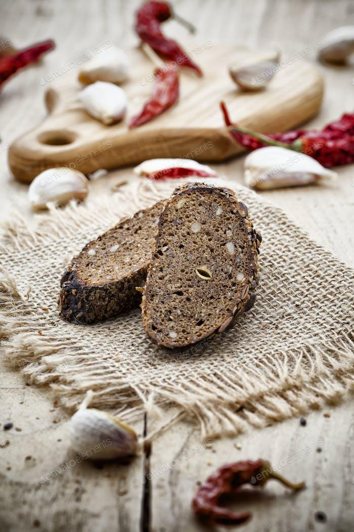 rebanada de pan de centeno y ají, ajo, sobre un fondo de madera.
