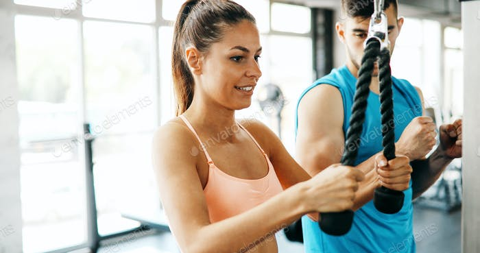 Personal trainer helping fit woman in gym