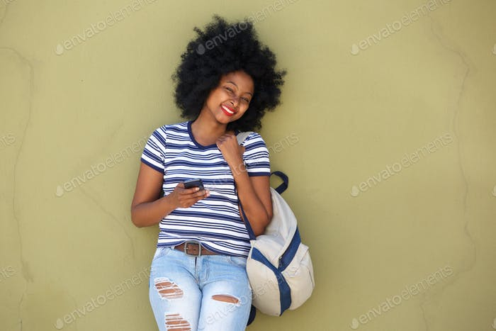 happy woman with smart phone and bag by wall
