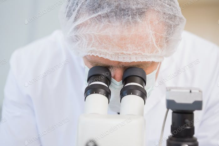 Scientist examining sample with microscope in the laboratory