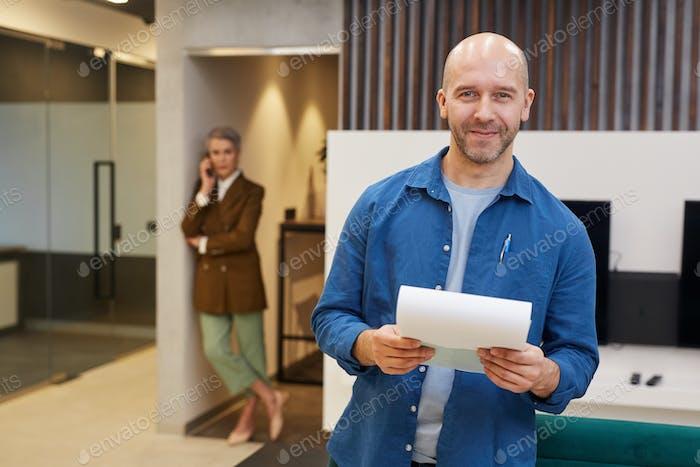 Lächelnder Erwachsener Mann hält Vertrag Papiere in Büro Lobby