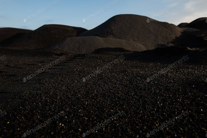 Hills of polluted, infertile and toxic dark soil with blue sky above and nobody around