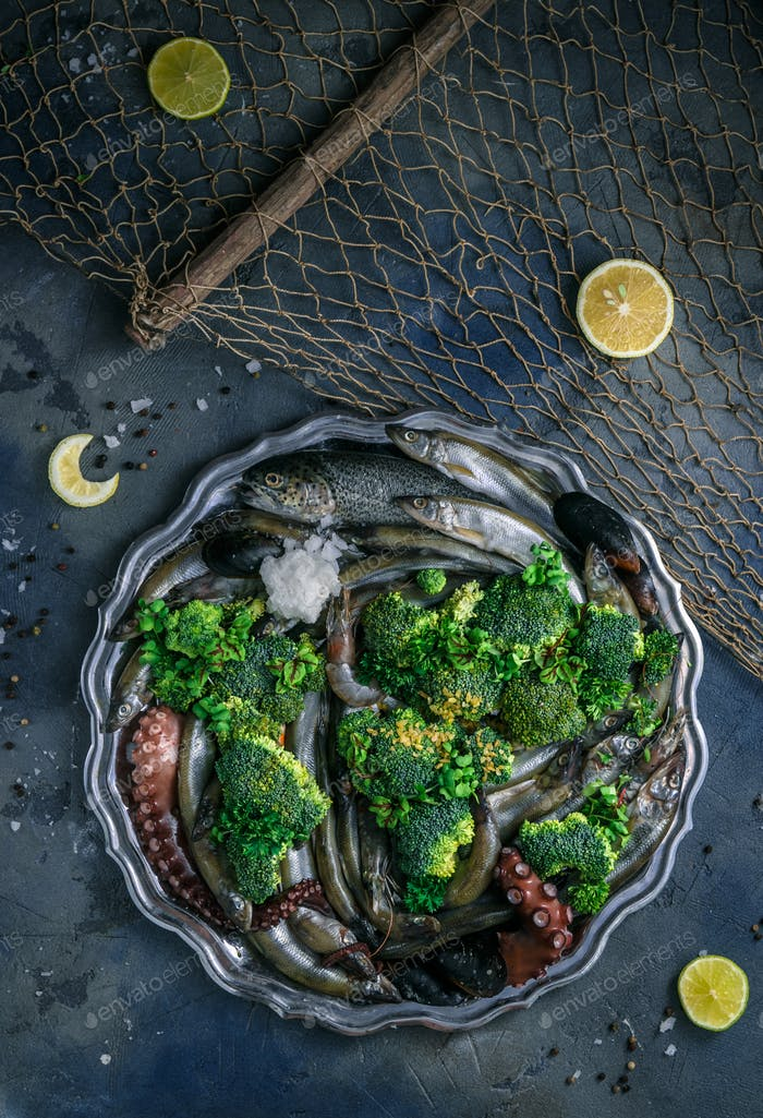 Raw Mixed seafood on a silver plate, dark background, copyspace