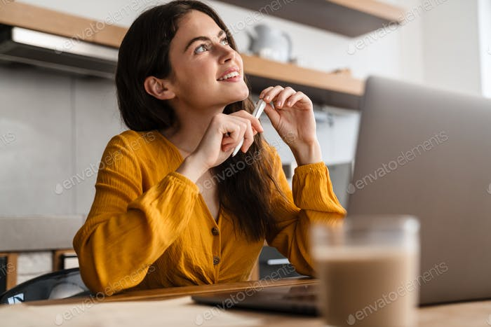 Young smiling woman working with laptop and papers at home kitchen