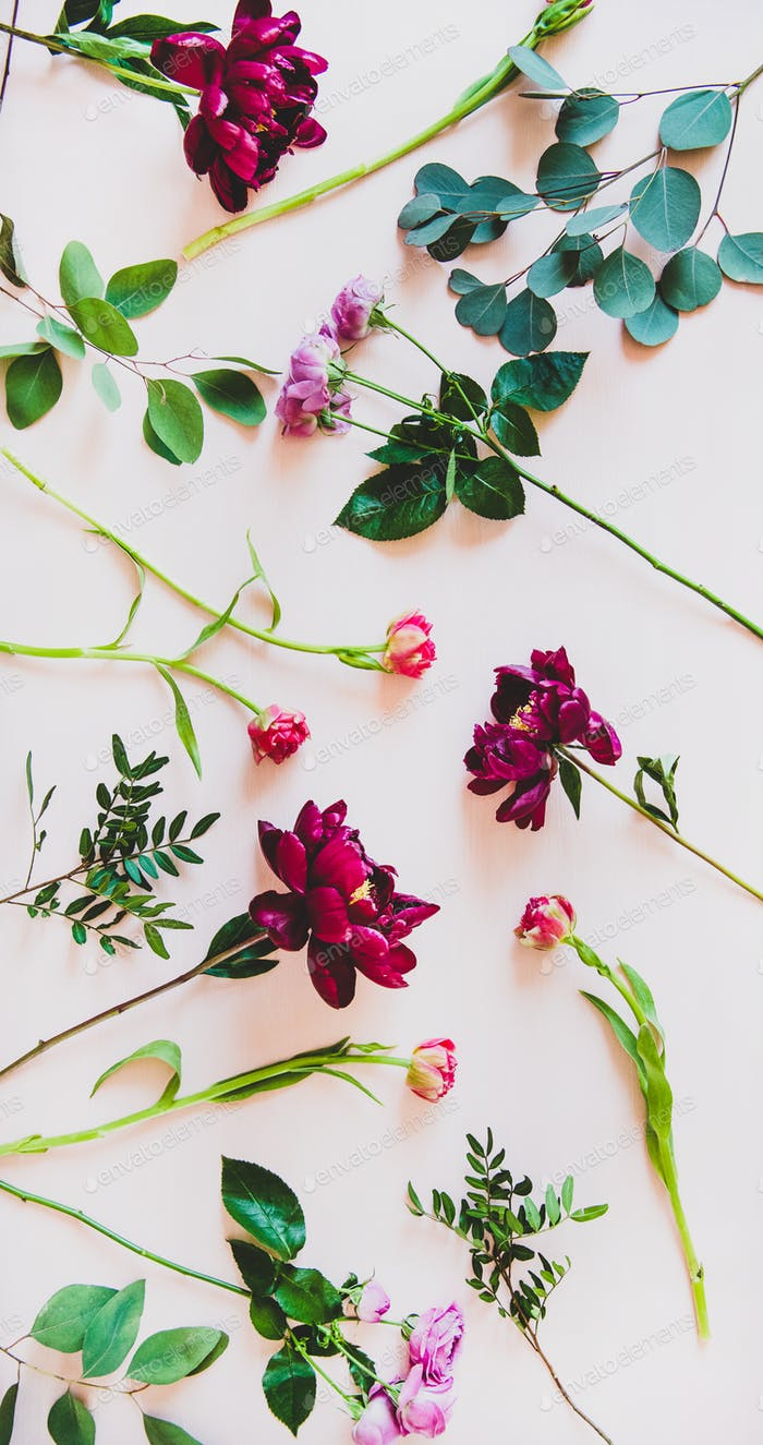 Flat-lay of various summer flowers over pink background, vertical composition