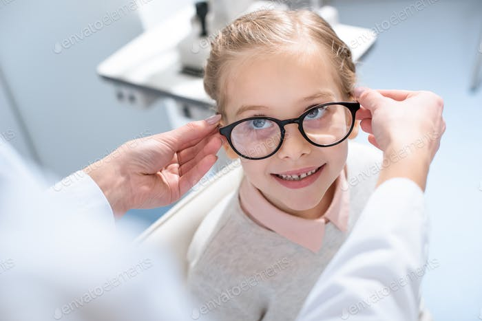 oculist and little child in glasses in optical clinic