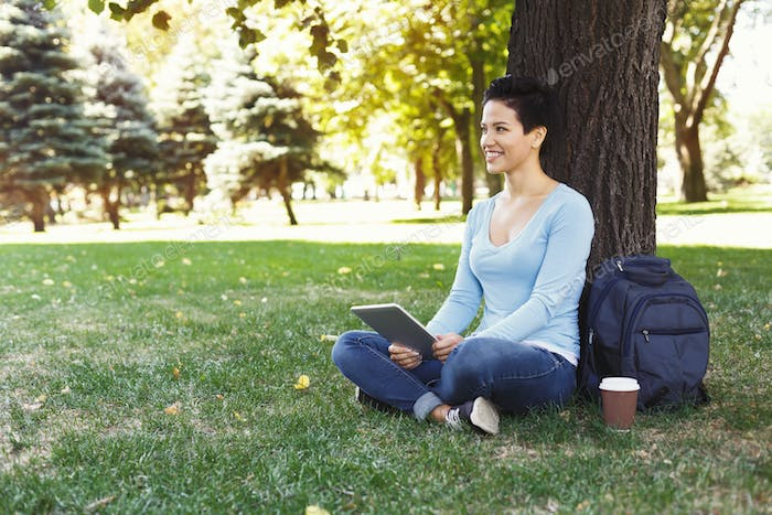 Woman sitting on the grass with digital tablet outdoors