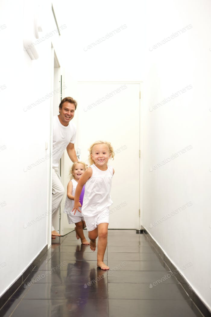 Cute little girls running at home with father