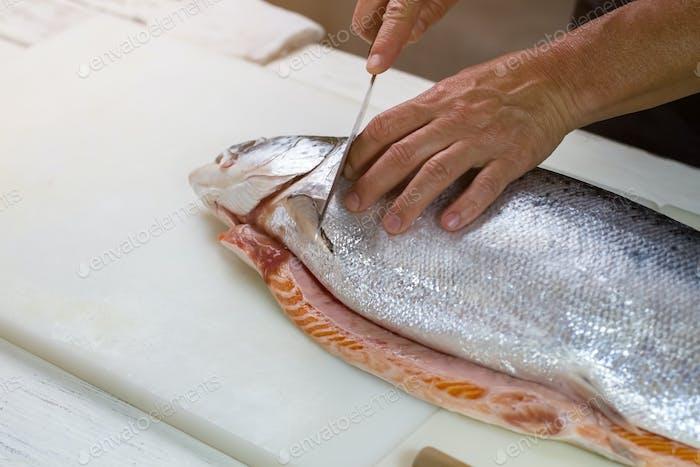 Knife cuts raw fish