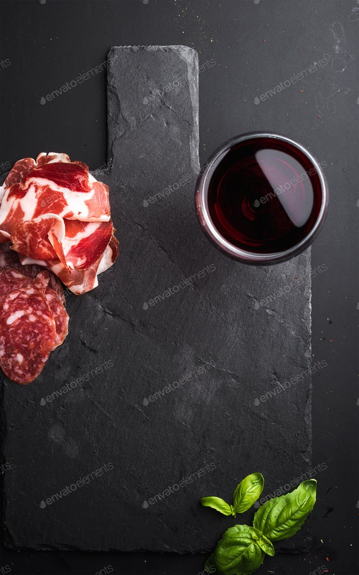 Glass of red wine, meat appetizer and basil on black  slate stone board over dark background