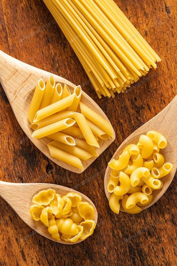 Various types of raw italian pasta in wooden spoons.