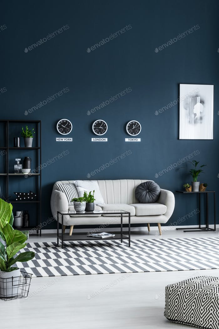White sofa, coffee table, clocks on the grey wall and striped ru