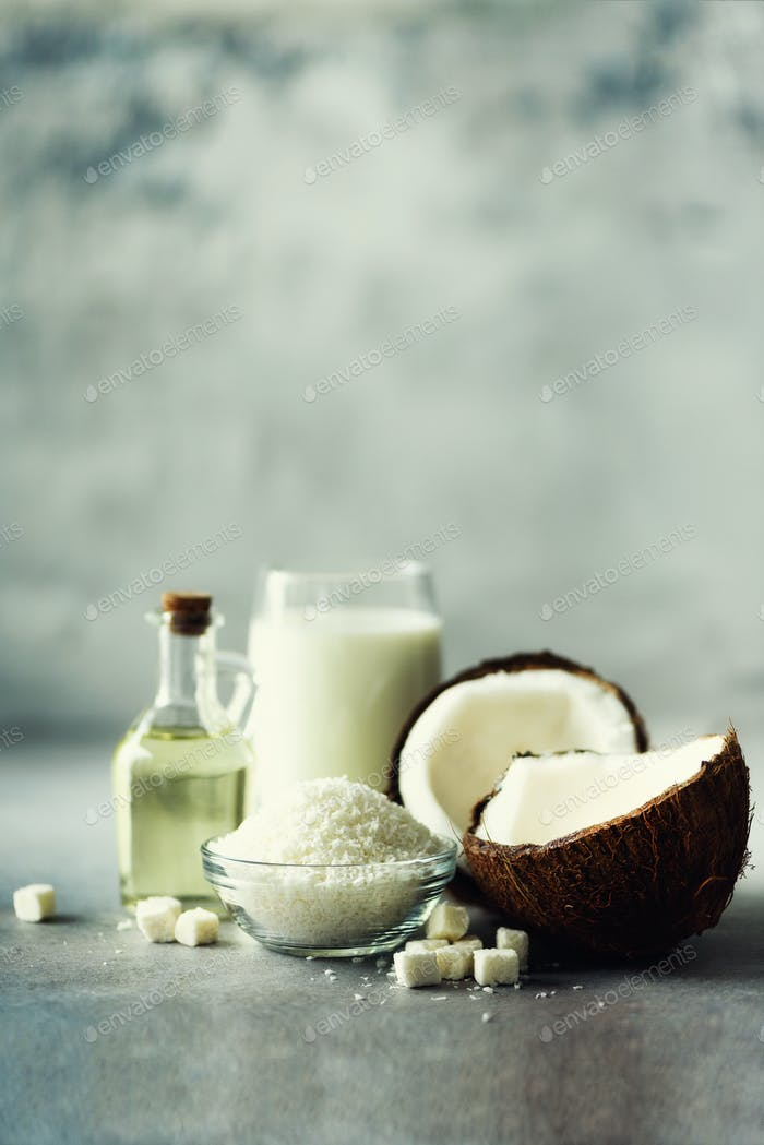 Coconuts products - milk, oil, shavings on grey concrete background. Copy space. Hair, skin and body
