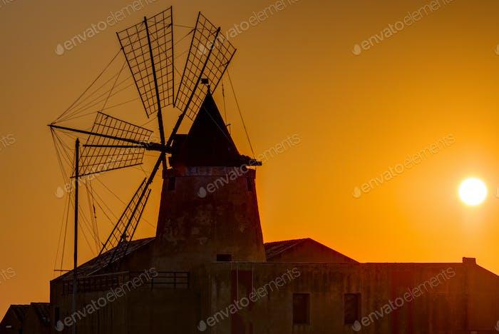 Windmühle bei Sonnenuntergang an den Salinen von Marsala