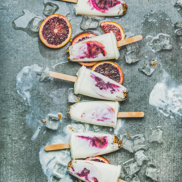 Red orange, yogurt, granola popsicles on ice cubes, square crop