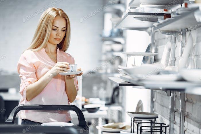 Frau in einer rosa Bluse kauft Gerichte im Laden