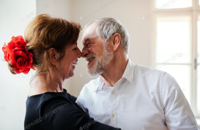 Affectionate senior couple attending dancing class in community center