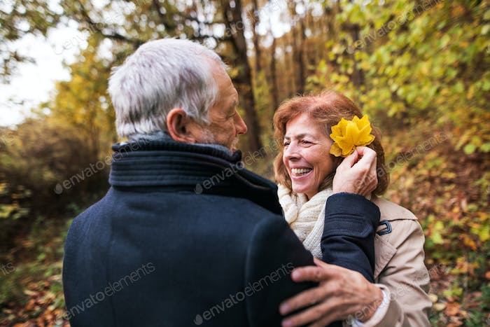 Senior man putting yellow leaves in woman's hair in forest in nature.