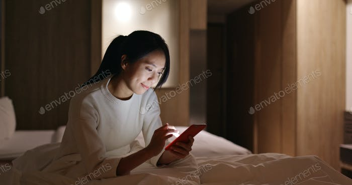 Woman uses mobile phone in bed at night