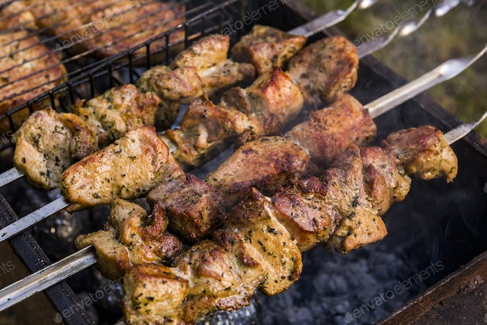 Grilled kebab cooking on metal skewers. Roasted meat cooked at barbecue